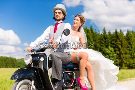 bridal pair driving motor scooter wearing