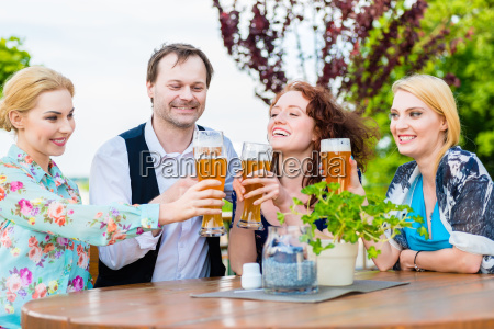 friends toasting with beer in garden