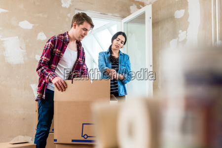 young woman bringing open box moving