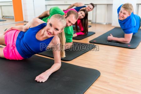 freizeitsportler die yoga uebungen im fitnessstudio