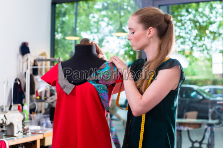 fashion designer draping dress on mannequin