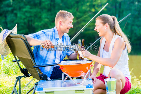 man and woman having barbeque grilling