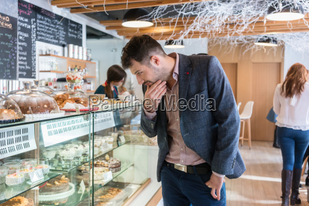 undecided man looking at various cakes