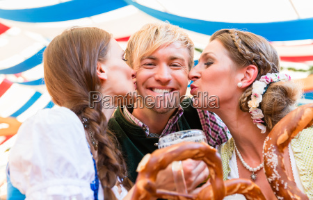 two women kissing man at bavarian