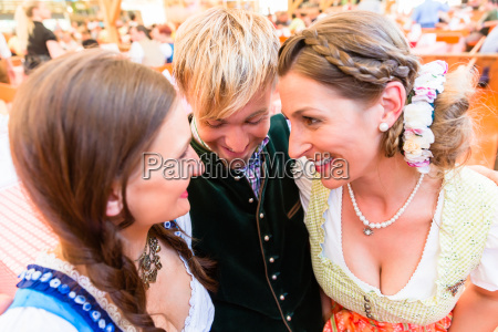 man hugging two dirndl wearing women