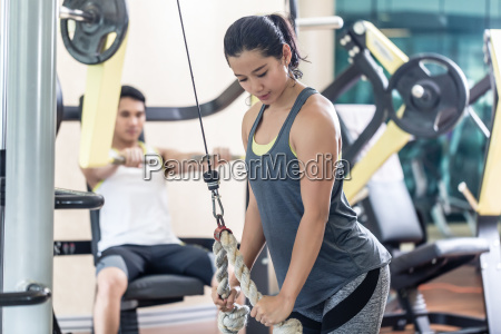determined young woman exercising cable rope