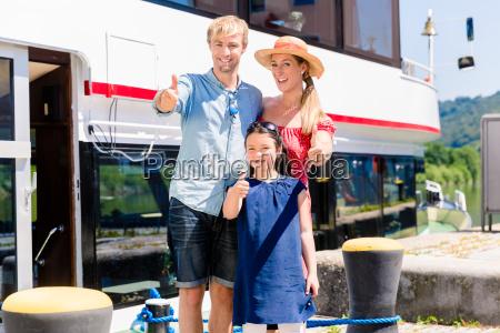 familie im urlaub vor boot zeigt