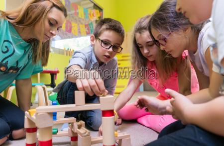 engagierte kindergartenlehrerin hilft kindern beim bau