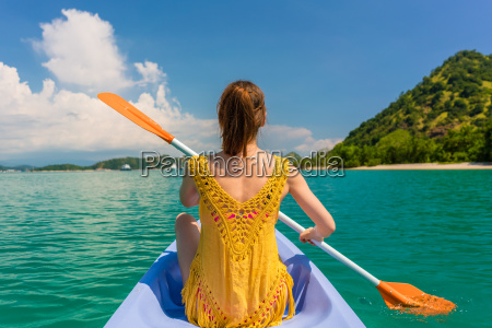 young woman paddling a canoe during