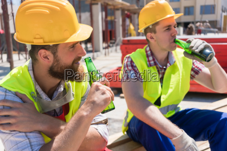 two young workers drinking a cold