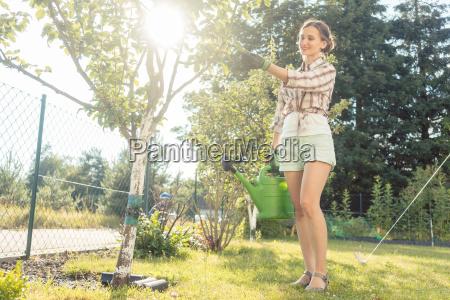 woman in her garden watering fruit