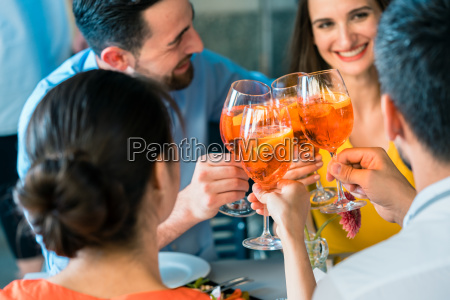 four friends toasting together with a