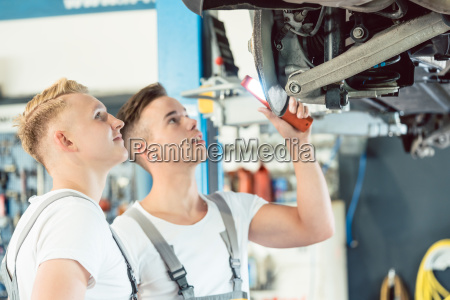 experienced auto mechanic teaching an apprentice