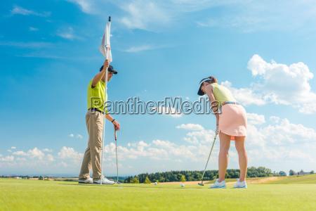 golfspielerin bereit den ball unter anleitung