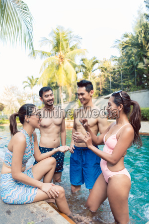 four young and cheerful friends talking