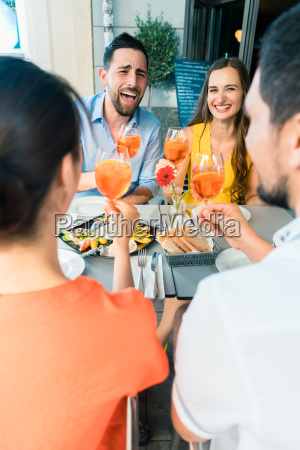 two happy young couples toasting while