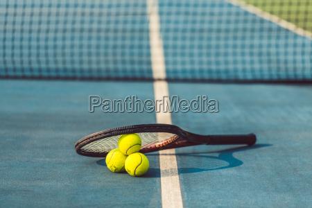 hochwinkelhautnah drei tennisbaelle auf einem profi