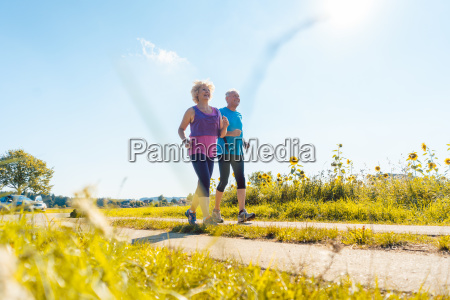 two healthy senior people jogging on