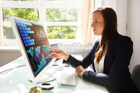 geschaeftsfrau analysiert graphen am computer