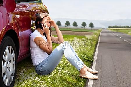 woman sitting on road near breakdown