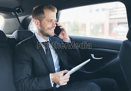 exekutivgeschaeftsmann an der rueckseite des autos