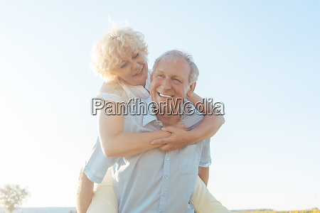 happy senior man laughing while carrying