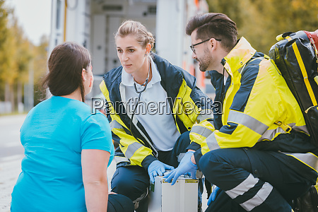 emergency medics talking to injured woman