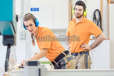 carpenter watching his apprentice working