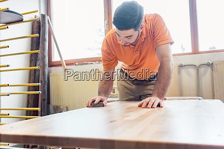 carpenter polishing and varnishing a table