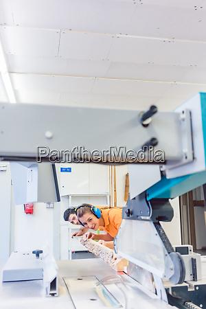 man and woman carpenter cutting board