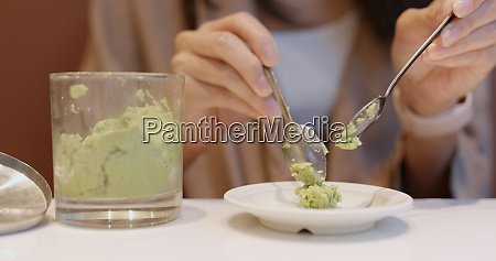 woman putting wasabi on plate in