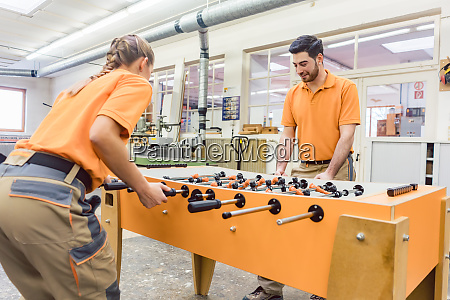 two carpenters playing table football in