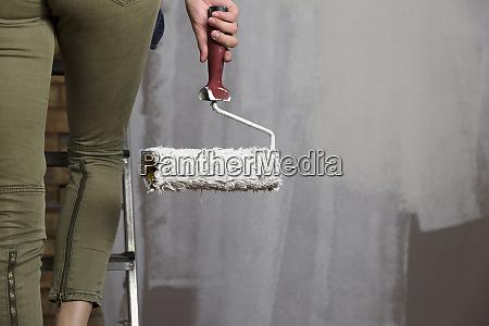 heimwerker schoene frauenmalereiwand mit farbenrolle