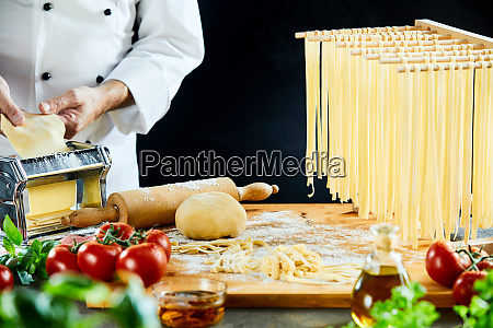 chef stretching out dough next to