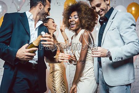mann oeffnet champagnerflasche auf feier im