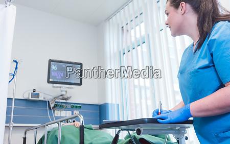 krankenschwester schreibt daten ueber patienten im