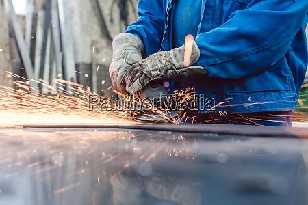 arbeiter in metallfabrik schleif werkstueck mit