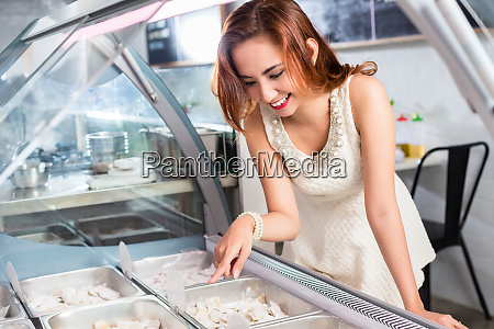 smiling woman selecting food from a