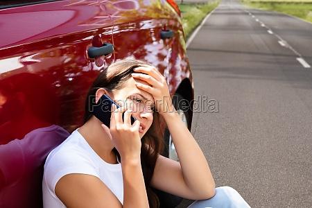 stressed woman using cellphone near breakdown