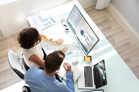 zwei wirtschaftler die diagramme auf computer