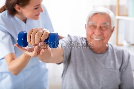nurse helping senior man with dumbbell