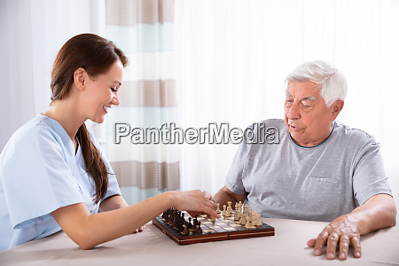 female caretaker playing chess with senior