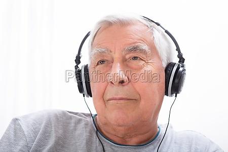 senior man hoert musik am kopfhoerer