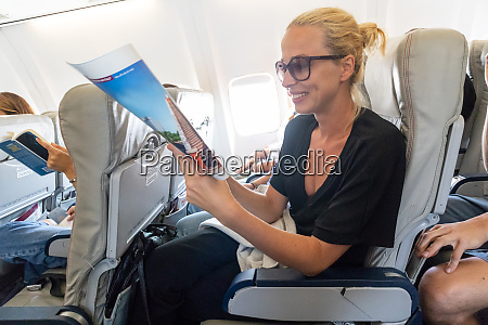 woman reading magazine on airplane during