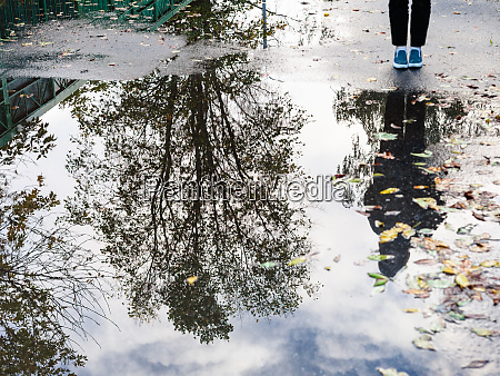 teenager near rain puddle with on