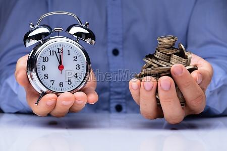 man holding alarm clock and golden