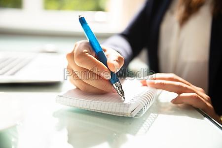 nahaufnahme von einer geschaeftsfrau es handschreiberungshand
