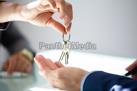 immobilienmakler giving house key to man