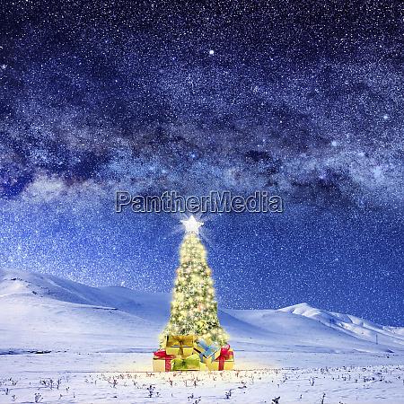 konzeptbild des geschmueckten weihnachtsbaums auf schneebedeckter