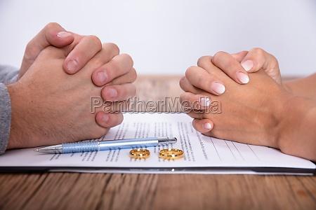 paarhand hand mit scheidungsvertrag und hochzeits
